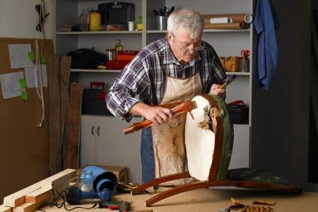 Ældre mand renoverer gammel stol